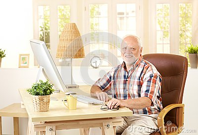 Senior man sitting at desk at home