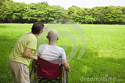 Senior man sitting on a wheelchair with his wife