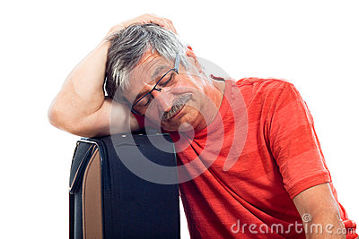 Senior man sleeping on luggage