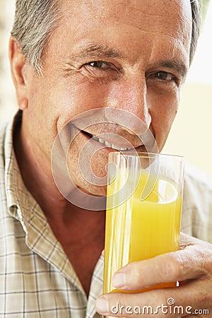 Senior Man Smiling Drinking Orange Juice