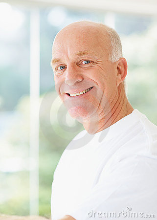 Senior man smiling over a bright background