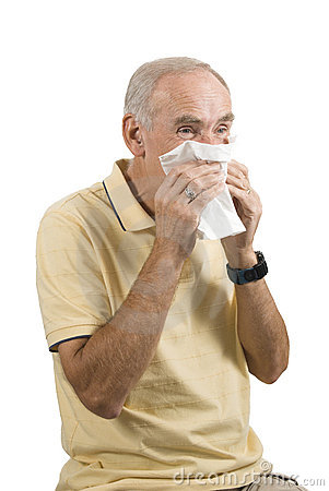 Senior man sneezing into handkerchief