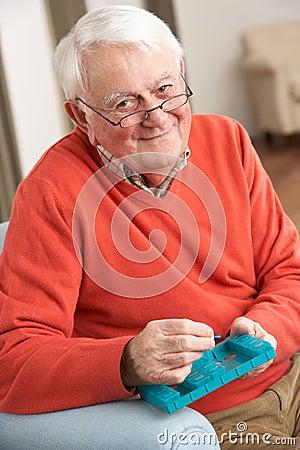 Senior Man Sorting Medication Using Organiser