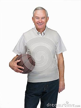 Senior man standing with basket ball against white