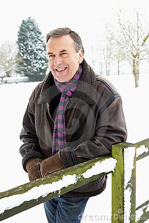 Senior Man Standing Outside In Snow Landscape