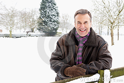 Senior Man Standing Outside In Snowy Landscape