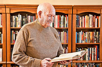 Senior Man Standing and Reading Book in Library