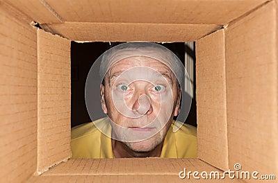 Senior man staring into cardboard box
