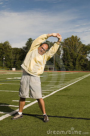 Senior man stretching exercising sports field