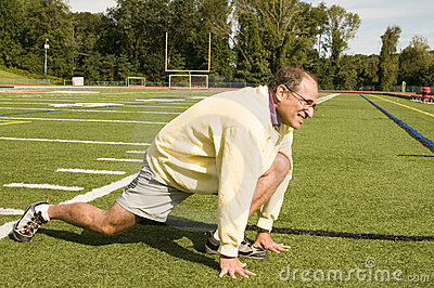 Senior man stretching exercising on sports field