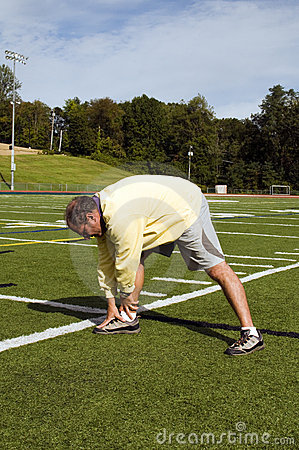 Senior man stretching sports field