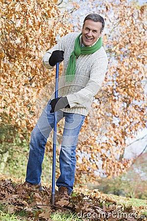 Senior man tidying autumn leaves