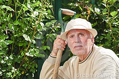 Senior man with tool in garden
