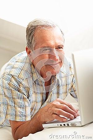 Senior Man Using Laptop Relaxing Sitting On Sofa