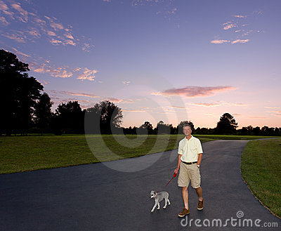 Senior man walking dog at sunset