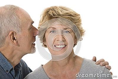 Senior man whispering in his wife s ear