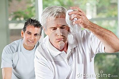 Senior man wiping sweat of his