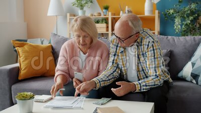 Senior man and woman counting money looking through bills busy with finance. Senior man and woman are counting money looking through bills busy with finance on stock video footage