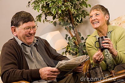 Senior man and woman couple reading newspaper