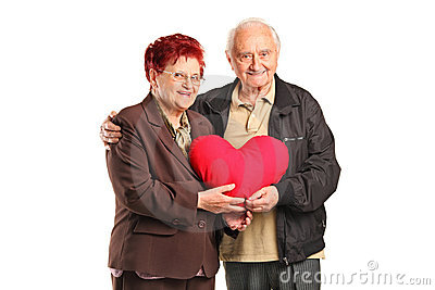 Senior man and woman holding a heart shaped pillow