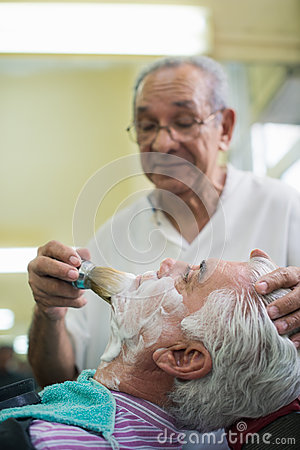 Senior man at work as barber shaving customer