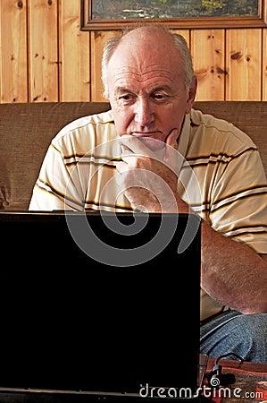 Senior man is working on laptop