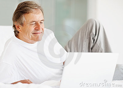 Senior man working on a laptop while in bed