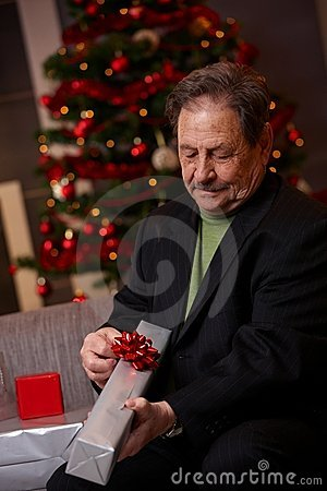 Senior man wrapping christmas present