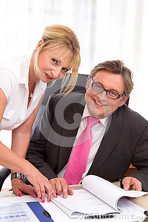 Senior managing director with his secretary at desk