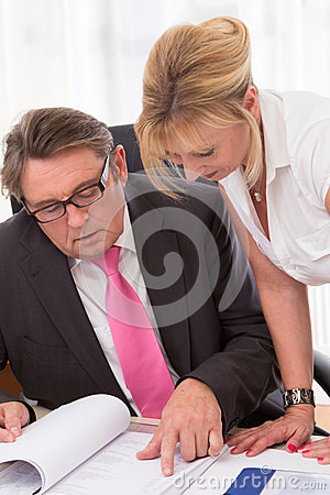 Senior managing director with his secretary at desk
