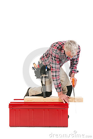 Senior manual worker sawing