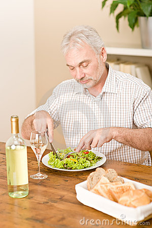 Senior mature man eat vegetable salad