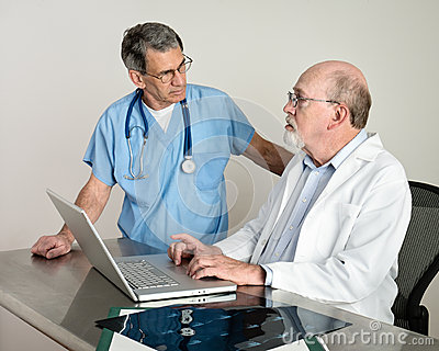 Senior Medical Doctors Discussing Patient s MRI Film Scans