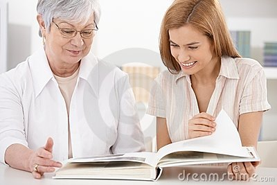 Senior mother and daughter looking at photo album