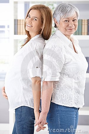 Senior mother and pregnant daughter smiling