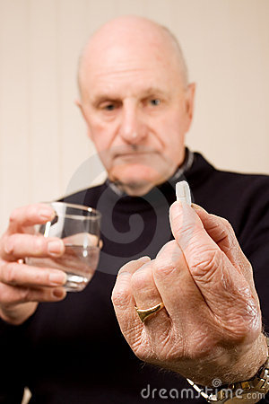 Senior older man holding tablet or pill with water