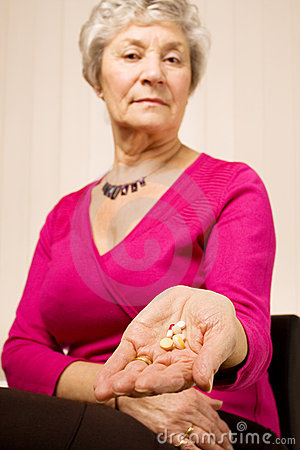 Senior older woman holding tablets or pills