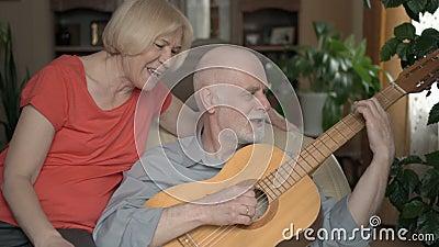 senior para w domu Mąż bawić się gitarę, żony obsiadanie na karle Śpiewający i ono uśmiecha się zbiory