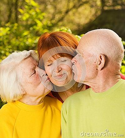 Senior parents kissing their daughter