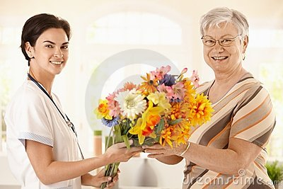 Senior patient giving flowers to nurse