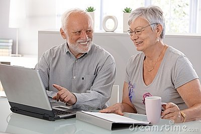 Senior people using laptop smiling