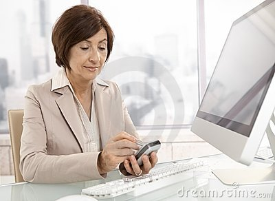 Senior professional woman using pda in office