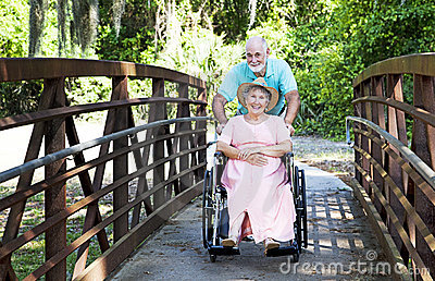 Senior Pushes Wife in Wheelchair