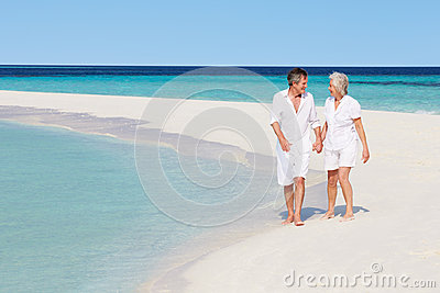 Senior Romantic Couple Walking On Beautiful Tropical Beach