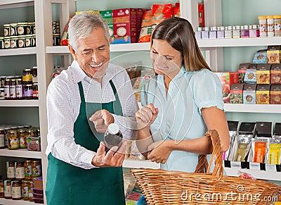 Senior Salesman Assisting Female Customer In