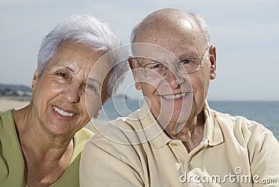 Senior smiling couple at the b