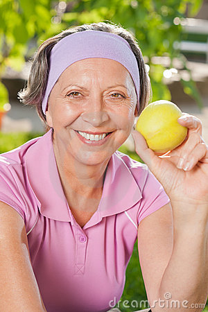 Senior sportive woman smile eat apple outdoor