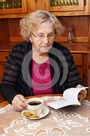 Senior with tea reading