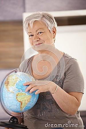 Senior teacher pointing at globe