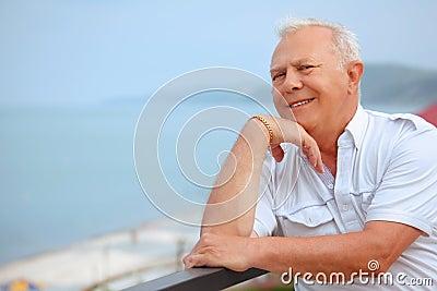 Senior on veranda, lean elbows about handrail